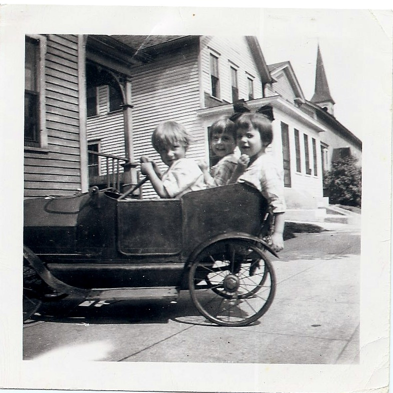 Three kids in toy car, 1919